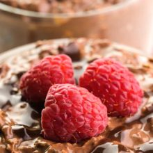 A closeup shot shows chocolate oatmeal in a bowl with chocolate drizzles and fresh raspberries on top. There's another bowl in the background. The text at the top of the image reads, Chocolate Overnight Oats.