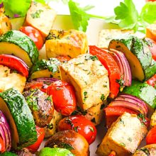Several grilled skewers are full of veggies and tofu sitting on a plate. There are fresh herbs around the plate, cherry tomatoes, and red onions. The text at the top of the image reads, Vegan Kebabs.